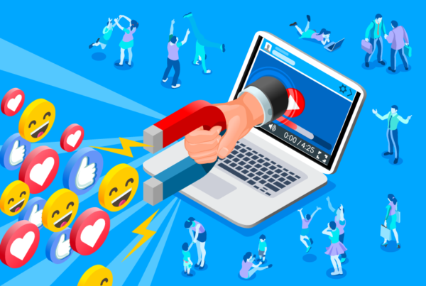 The Psychology behind Social Media Engagement: How to Use it to Your Advantage. An image of a silver laptop with a hand coming out of the screen. The hand is holding a blue and red magnet and is attracting a group of smiling emojis, love heart emojis, and thumbs up emojis.