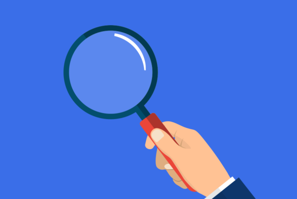 How to craft your buyers personas blog. An graphic of a magnifying glass being held against a blue background